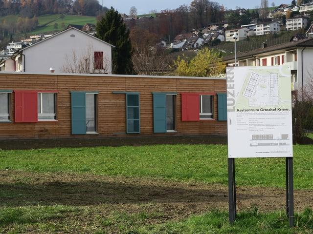 Holzbaracke mit grünen und roten Fensterläden.