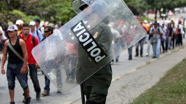 Ein kolumbianischer Polizist im Vordergrund, dahinter sind Protestierende.