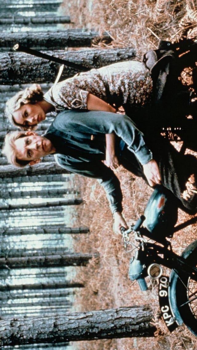 Ein Mann und eine Frau auf einem Moped im Wald. Die Frau trägt ein Gewehr auf dem Rücken.