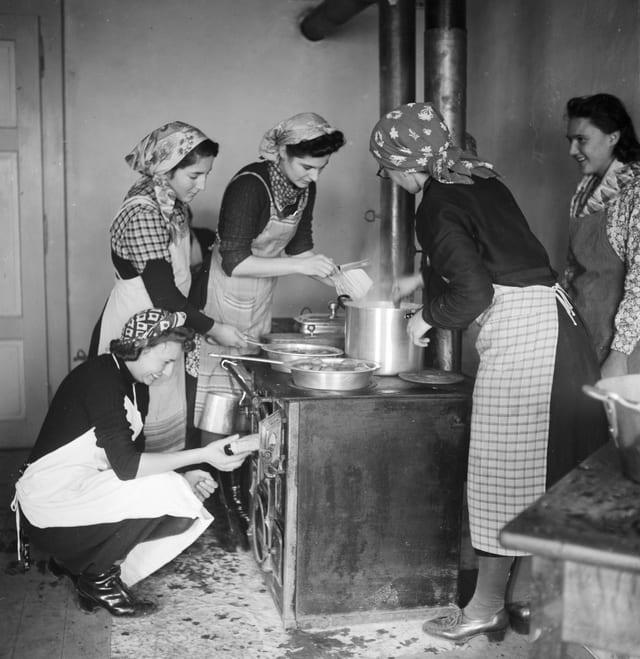 """Frauen touren mit sogenannten """"Fahrende Küchen"""" durch die Dörfer um in jenen, welche keine eigene Haushaltungsschule haben, Haushaltungsunterricht zu erteilen. Junge Frauen beim Unterricht im Dorf Ardon im Wallis."""