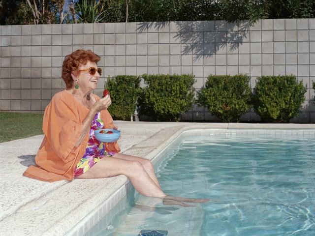 Ältere Frau isst Erdbeeren am Pool.