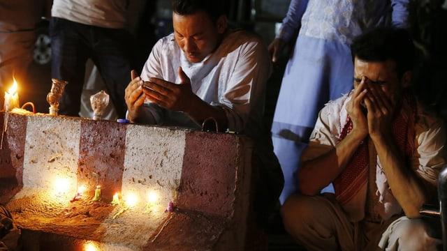 Sitzende Afghanen beten für die Opfer, vor ihnen Kerzen