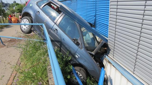 Blaues Personenfahrzeug liegt in einem Graben zwischen Trottoir und Hauswand. Der Motorenraum ist eingedrückt.