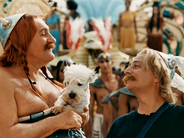 The film scene from Asterix and Obelix. They both face each other and look at each other. Obelix holds the dog Idefix in hand.