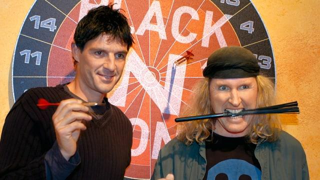 Roman Kilchsperger und Chris von Rohr posieren Grimassen schneidend vor einem Dartbrett.