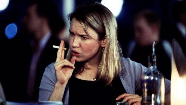 Filmszene: Eine junge Frau sitzt an einem Tisch und raucht. Vor ihr steht eine Flasche Vodka.
