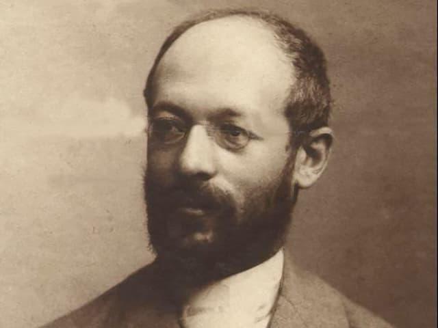 Schwarzweissfotto eines Mannes mit Vollbarrt, Stirnglatze und Nickelbrille.