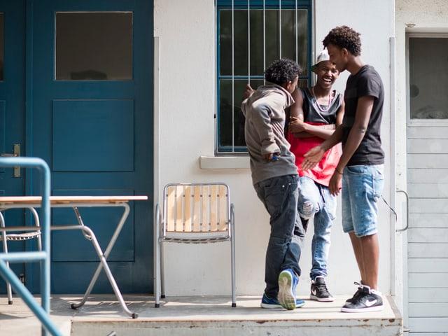 Drei schwarze Männer stehen vor einem Haus.