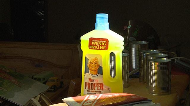 Eine Flasche Putzmittel steht zwischen Büchsen und Spielzeug.