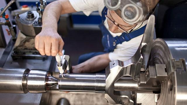 Symbolbild: Ein Mechaniker arbeitet an einem grossen Drehstück.
