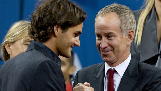 John McEnroe schüttelt Roger Federer die Hand.