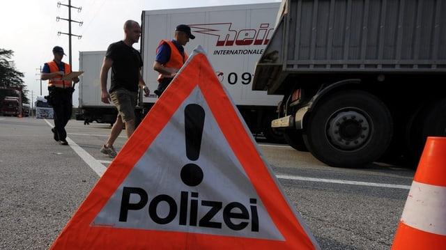 Polizisten kontrollieren einen Lastwagen
