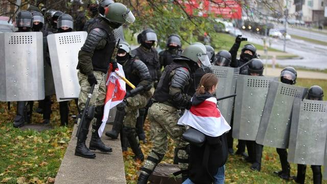 Polizisten in Vollmontur führen eine junge Frau mit rot-weiss-roter Flagge ab.