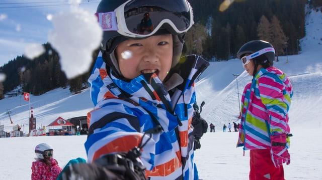 In uffant chinais sin skis che bitta ina borla da naiv.