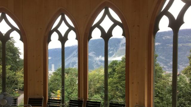 Helle Holzwände und kunstvoll gestaltete Fenster, im Pavillon stehen Stühle.
