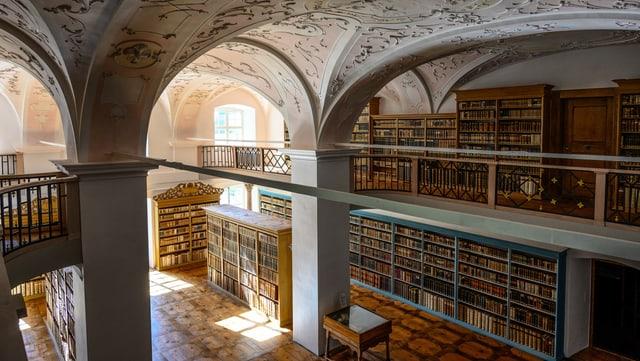 In einem schönen Raum stehen unzählige Regale voller Bücher.