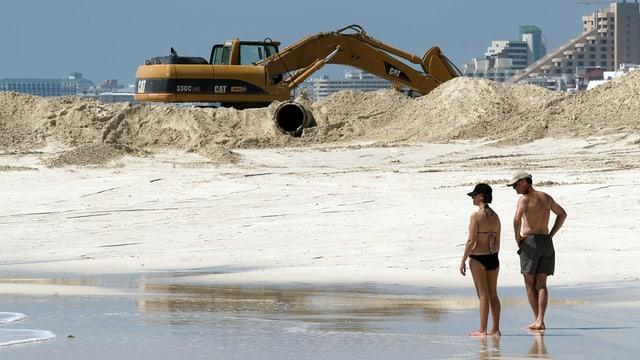 Menschen am Strand beobachten einen Bagger, der den Sand aufschaufelt