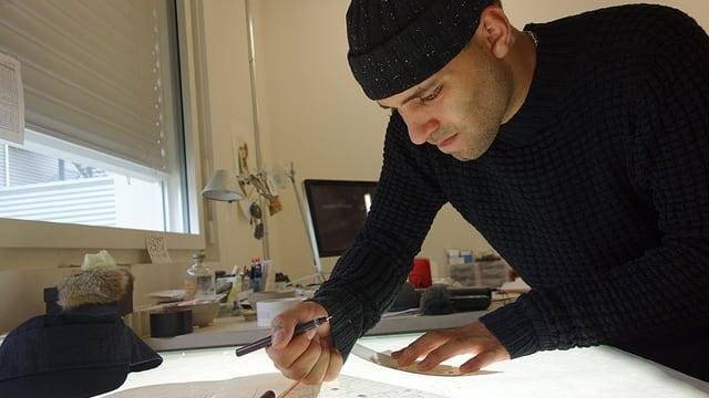 Sandro Marzo beugt sich auf einem Leuchttisch über ein Schnittmuster.