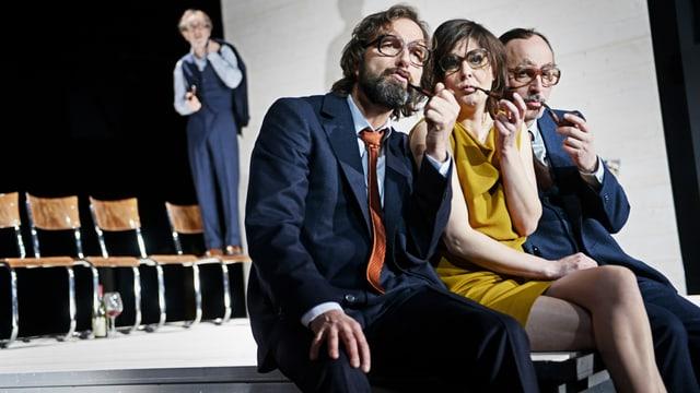 Drei Schauspieler und eine Schauspielerin mit Brillen und Tabakpfeifen auf der Theaterbühne