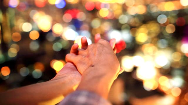 Zwei Hände verschränkt vor einem Lichtermeer.