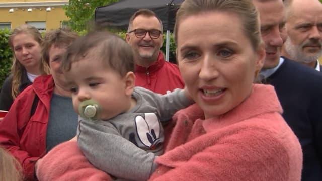 Mette Frederiksen mit einem Kind auf dem Arm.