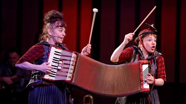Zwei Clowninnen mit einem überlangen Akkordeon in der Hand.