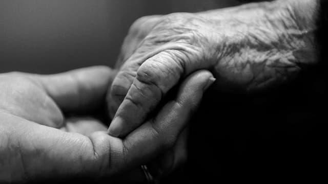 Alte Menschen halten Hände
