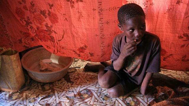 Ein dunkelhäutiges Kind aus Uganda sitzt in einem Zelt.