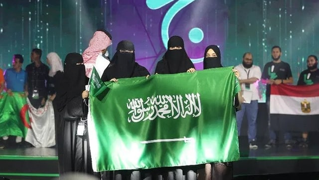 Vier verschleierte Frauen halten bei einer Preisverleihung. die Landesfahne Saudi-Arabiens in die Kamera.