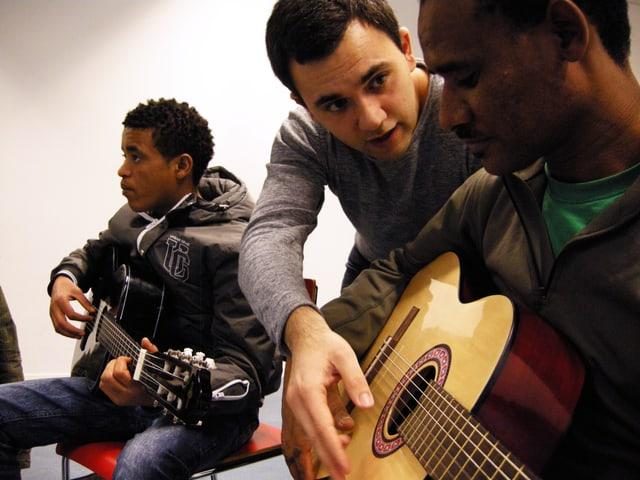 Jugendarbeiter Marco Martina übt mit Flüchtlingen Gitarre spielen.