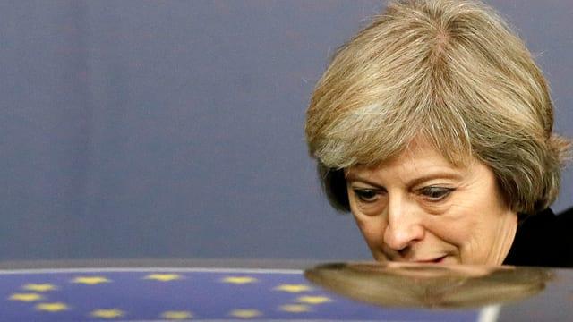 Theresa May steigt in ein Auto ein, auf dem Dach spiegelt sich die EU-Fahne.