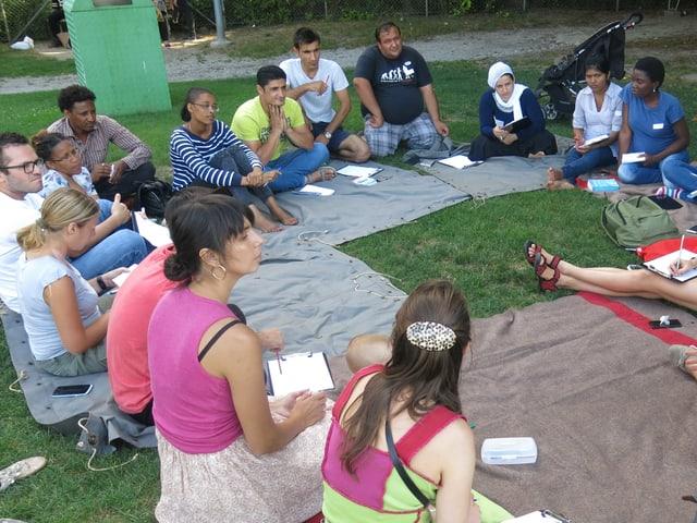 Sprachschüler sitzem im Freien im Kreis.