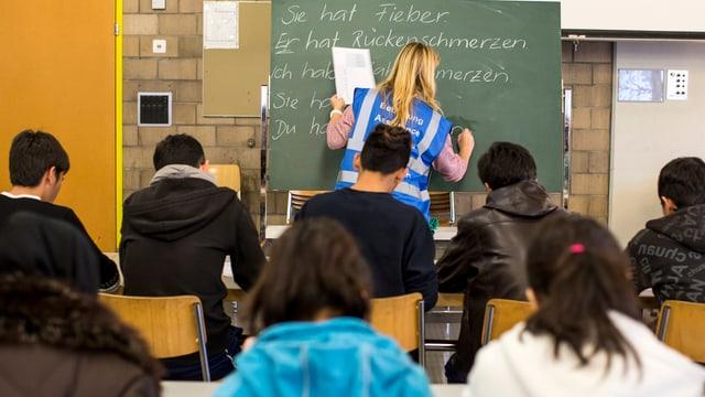 Deutschunterricht im Bundesasylzentrum Glaubenberg in Sarnen. Die Lehrerin schreibt etwas an die Tafel.