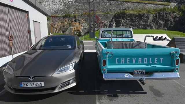 Ein Elektroauto parkt neben einem Lastauto.