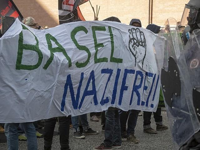Demonstranten mit Banner vor Polizisten