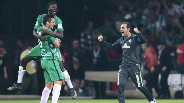 Coach Alexander Nouri und zwei Bremer Spieler jubeln nach dem Schlusspfiff ausgelassen