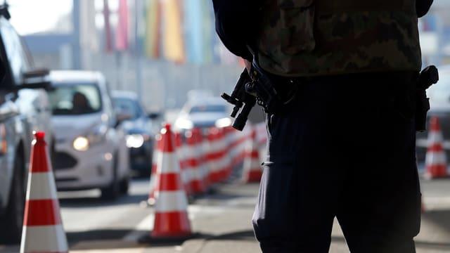 Polizist mit gesenkter Waffe neben Autokolonne
