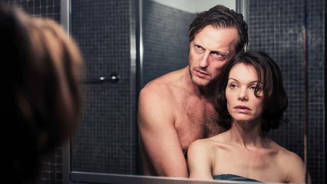 Ein Mann und eine Frau stehen nackt vor einem Badezimmer-Spiegel