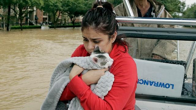 Junge Frau mit Katze auf einem Boot