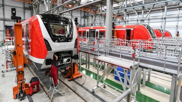 Bombardier Transportation in Deutschland, Blick ins Produktionslager, wo Arbeiter an zwei Zügen arbeiten.