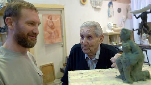 Jastrebenezki bespricht das Modell einer Skulptur mit einem jungen Mann.