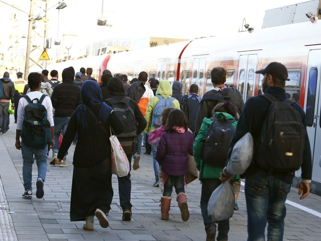 Flüchtlinge bewegen sich nach ihrer Ankunft in Richtung Haupthalle des Bahnhofs.