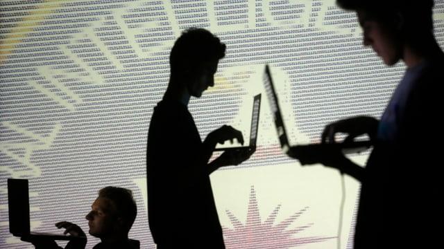 Die Silhouette von drei Männern, die am Laptom sind.