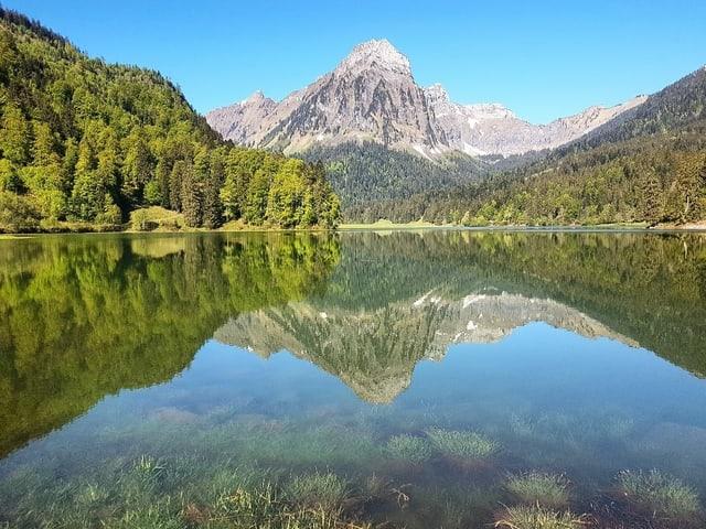Blick auf einen Bergsee unter blauem Himmel