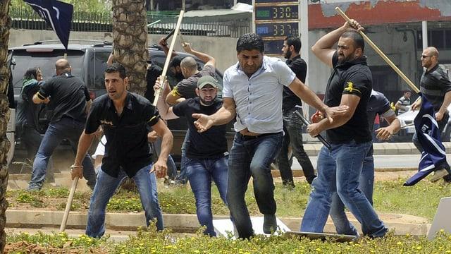 Hisbollah-Anhänger und -Gegner schlagen sich vor der iranischen Botschaft in Beirut. (keystone)