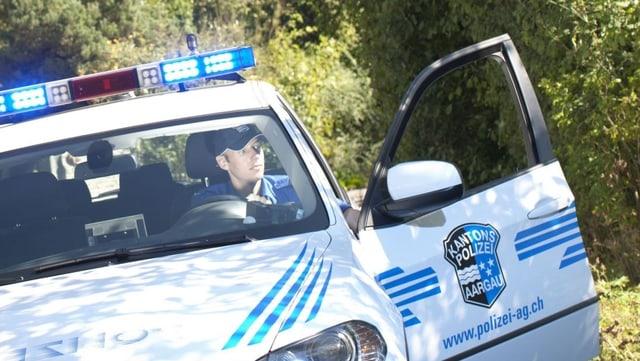 Polizeiauto hält im Wald, ein Polizist steigt aus.