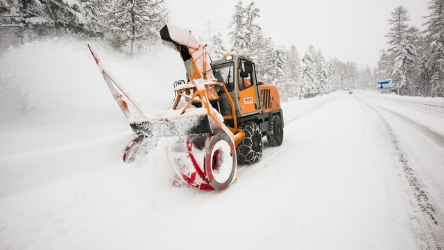 Ein Schneeräumungsfahrzeug im Einsatz auf einer verschneiten Strasse.