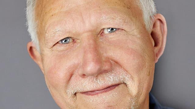 Ein lcähelnder älterer Herr mit grauen Haaren.