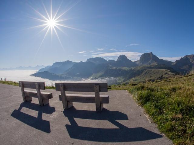 Zwei Ruhebänke am Berg, mit Ausblick über das Nebelmeer.