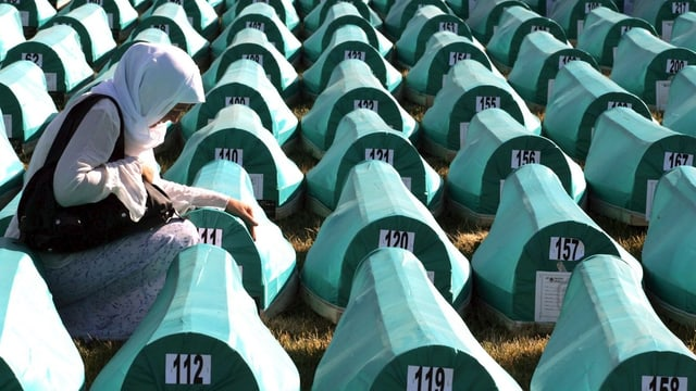 Eine Frau kniet vor einer Reihe von grün überdachten, nummerierten Särgen.